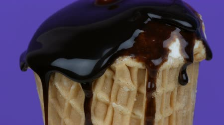 şurup : Chocolate sauce icing flows over ice cream in a waffle cup on pink background Stok Video