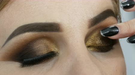 füstös : Master make-up artist apply professional make-up golden smoky eyes in beauty salon to a fat woman model with blue eyes close up Stock mozgókép