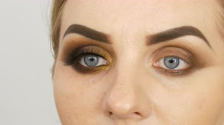 füstös : Master make-up artist apply professional make-up golden smoky eyes in beauty salon to a fat woman model with blue eyes