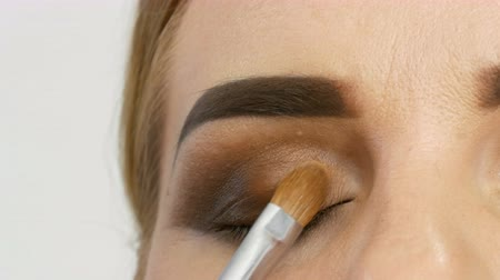 лайнер : Professional master makeup artist applies beige eyeshadow with special brush on model eye at beauty salon close up view