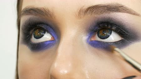 yanliŞ : Young beautiful sexy girl models make blue evening make up smoky eyes and with false eyelashes. Eyes with multi-colored contact lenses Stok Video