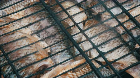 crucian : Freshwater river fish crucian carp Carassius fried on fire and smoke grill close up view. Delicious grilled fish on the fire