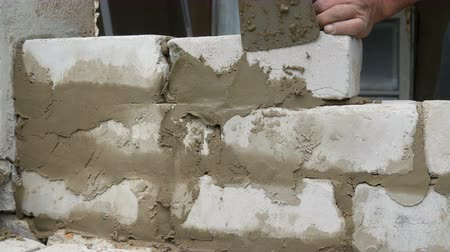 construtor : Male builder laying white brick on cement and standing wall. Hands of man laying building bricks close up view