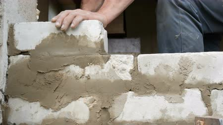 cálcio : Male builder laying white brick on cement and standing wall. Hands of man laying building bricks close up view