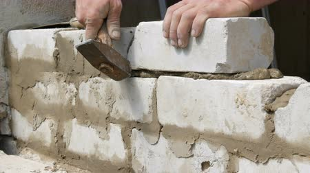 pedreiro : Male builder laying white brick on cement and standing wall. Hands of man laying building bricks close up view