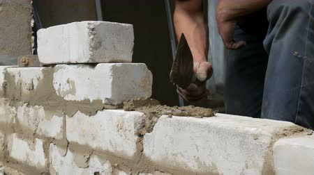 kielnia : Male builder laying white brick on cement and standing wall. Hands of man laying building bricks close up view