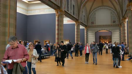 хозяин : AMSTERDAM, NETHERLANDS - 25 April, 2019: People take pictures on the mobile phone and watching famous pictures, in Rijksmuseum. Crowd tourist interested in art.