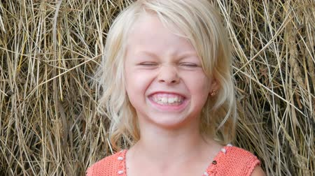 irritáció : Portrait of a cute smiled makes a face and laugh blue-eyed blonde seven-year-old girl with a dirty face child on a street outside the city on a summer day Stock mozgókép