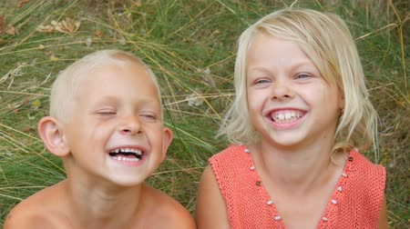 tur : Funny dirty faces children blonde brother and sister make faces laugh smile and have fun in village on nature on a summer day