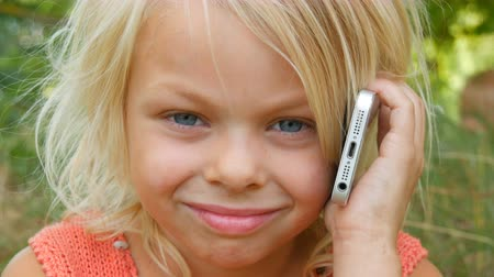 sete : Portrait of a cute blue-eyed blonde seven-year-old girl with dirty face laughing while talking on a mobile phone
