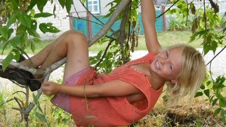 sete : Seven-year funny dirty child girl blonde hangs on a tree branch outside the city on summer day Vídeos