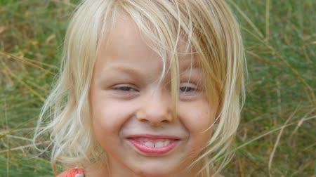gesztus : Portrait of a cute smiled and laugh blue-eyed blonde seven-year-old girl with a dirty face child on a street outside the city on a summer day
