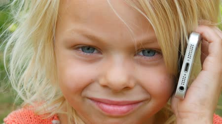 скрывать : Portrait of a cute blue-eyed blonde seven-year-old girl with dirty face laughing while talking on a mobile phone