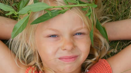 sete : Cute blue-eyed blonde seven-year-old girl with a dirty face. Child is lying on the grass with her hands behind her head chewing dry straw. Close up face