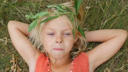 sete : Cute blue-eyed blonde seven-year-old girl with a dirty face. Child is lying on the grass with her hands behind her head chewing dry straw.