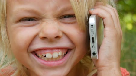 fool : Portrait of a cute blue-eyed blonde seven-year-old girl with dirty face laughing while talking on a mobile phone