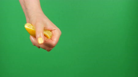dilimleri : Female hand with yellow manicure squeezes out half a lemon on green chroma key background Stok Video