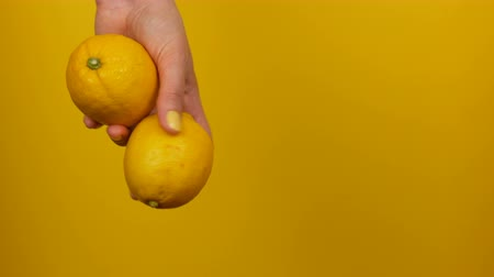 cuisine dark : Female hand with yellow manicure holds two lemons on yellow background