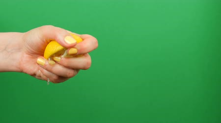 cripple : Female hand with yellow manicure squeezes out half a lemon on green chroma key background Stock Footage