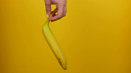 очищенные : Female hand with yellow manicure holds a ripe banana fruit on yellow background Стоковые видеозаписи