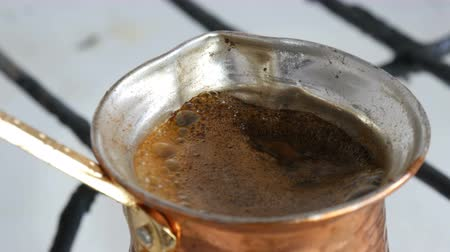 capacidade : Ground black coffee in a copper Turk is brewed and boils on a gas stove. Barista preparing hot tasty drink at home close up