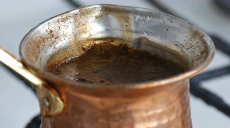 turk : Ground black coffee in a copper Turk is brewed and boils on a gas stove. Barista preparing hot tasty drink at home close up