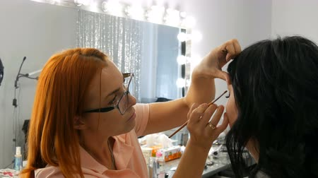 ruj : Red-haired stylist make-up artist doing stylish evening make-up of model with long black hair in beauty salon Stok Video