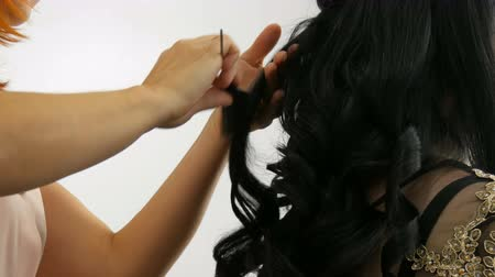 rozšíření : Long beautiful black hair curler stylist curls. Hair styling and curling. Hair Extension Capsules on the head