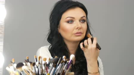 kızarmak : Portrait of a beautiful blue-eyed woman model with long black hair sitting in front of mirror and adjusts makeup using a special powder brush