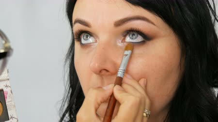 vurgulayıcı : Portrait of a beautiful blue-eyed woman model with long black hair who is doing evening brown eye makeup and eyebrow with special brush