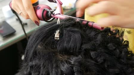 frizura : Hairdresser stylist makes a special curl small curly hair with special curling iron Stock mozgókép