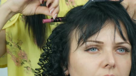 головной убор : Hairdresser stylist makes a special curl small curly hair with special curling iron Стоковые видеозаписи