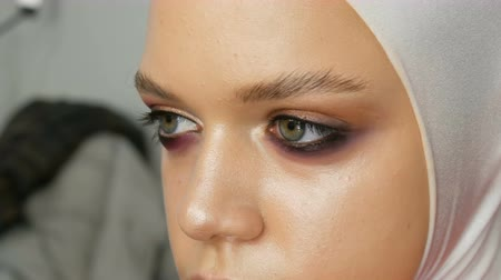 arcszín : Woman make-up artist stylist makes makeup fashionable pink smoky eyes with special makeup brush of young model