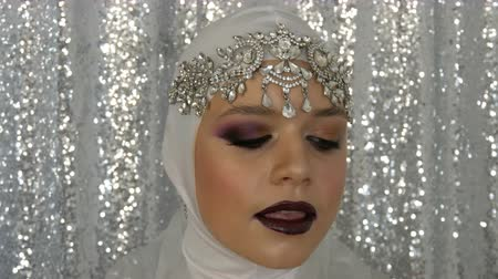 tiara : Face of model in a white image and a silver tiara with bright multi-colored make-up called a smoky eye, posing in front of the camera in model agency on a silver background. High fashion