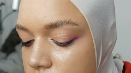 eyeshade : Woman make-up artist stylist makes makeup fashionable pink smoky eyes with special makeup brush of young model