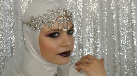 átalakítása : Face of model in a white image and a silver tiara with bright multi-colored make-up called a smoky eye, posing in front of the camera in model agency on a silver background. High fashion