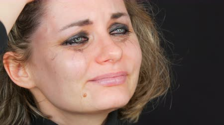 разочарование : Beautiful young tearful unhappy woman crying washing off makeup. Real tears running down on face that screams of desperation in hysterics in black jacket on a black background, face close up view
