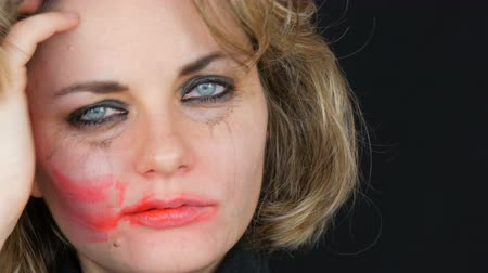 fájó : Tearful depressive crazy young woman with smeared makeup looking at camera red lipstick smears with hand