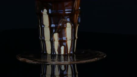 покрытый : Melting ice cream on which pours chocolate syrup sauce on black background