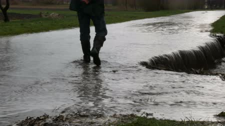 perna : Disaster. Flooding in the village. Dirty black rivers flow along the road. Man in black rubber boots walks through the puddles. Stock Footage