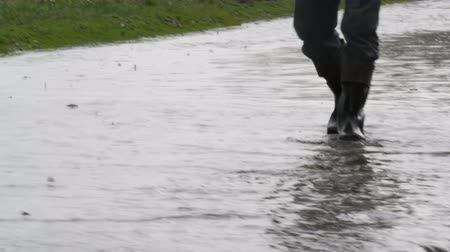 tragédia : Disaster. Flooding in the village. Dirty black rivers flow along the road. Man in black rubber boots walks through the puddles. Stock mozgókép
