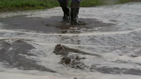 submerso : Disaster. Flooding in the village. Dirty black rivers flow along the road. Man in black rubber boots walks through the puddles. Stock Footage