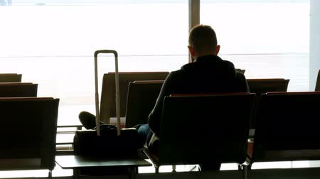 urlop : Silhouette of a man with suitcase waiting at the airport before departure Wideo