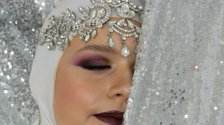 preparált : Professional model in a white image and a silver tiara with a bright multi-colored make-up called a smoky eye, posing in front of the camera in model agency on a silver background. High fashion