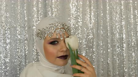 diadeem : Face of model and tulip in a white image and a silver tiara with bright multi-colored make-up called a smoky eye, posing in front of the camera in model agency on a silver background. High fashion Stockvideo