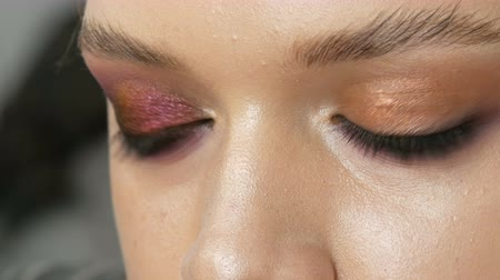 füstös : High-fashion. Makeup artist making professional make-up smoky eyes of pink and black color for girl model for shooting in the studio. Close up view of green eye model