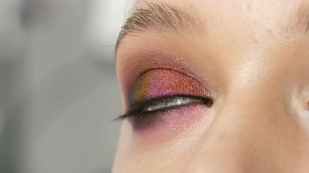 tusz do rzęs : High-fashion. Makeup artist making professional make-up smoky eyes of pink and black color for girl model for shooting in the studio. Close up view of green eye model
