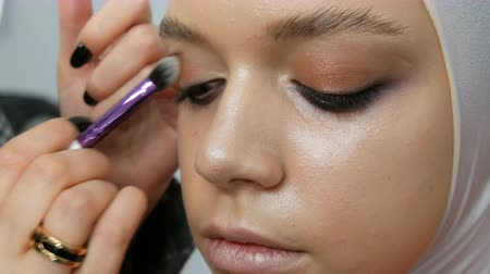 ショー : Woman make-up artist stylist makes makeup fashionable pink smoky eyes with special makeup brush of young model