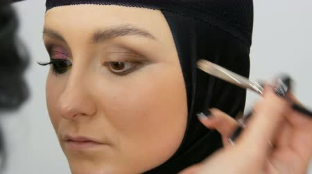 bulva oční : Professional stylist make-up artist makes eye makeup model. Face model with evening makeup close up view