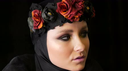 hearse : Professional girl model with beautiful makeup poses in a black cap and wreath on her head in front of the camera on black background in the image of a black widow. High-fashion Stock Footage